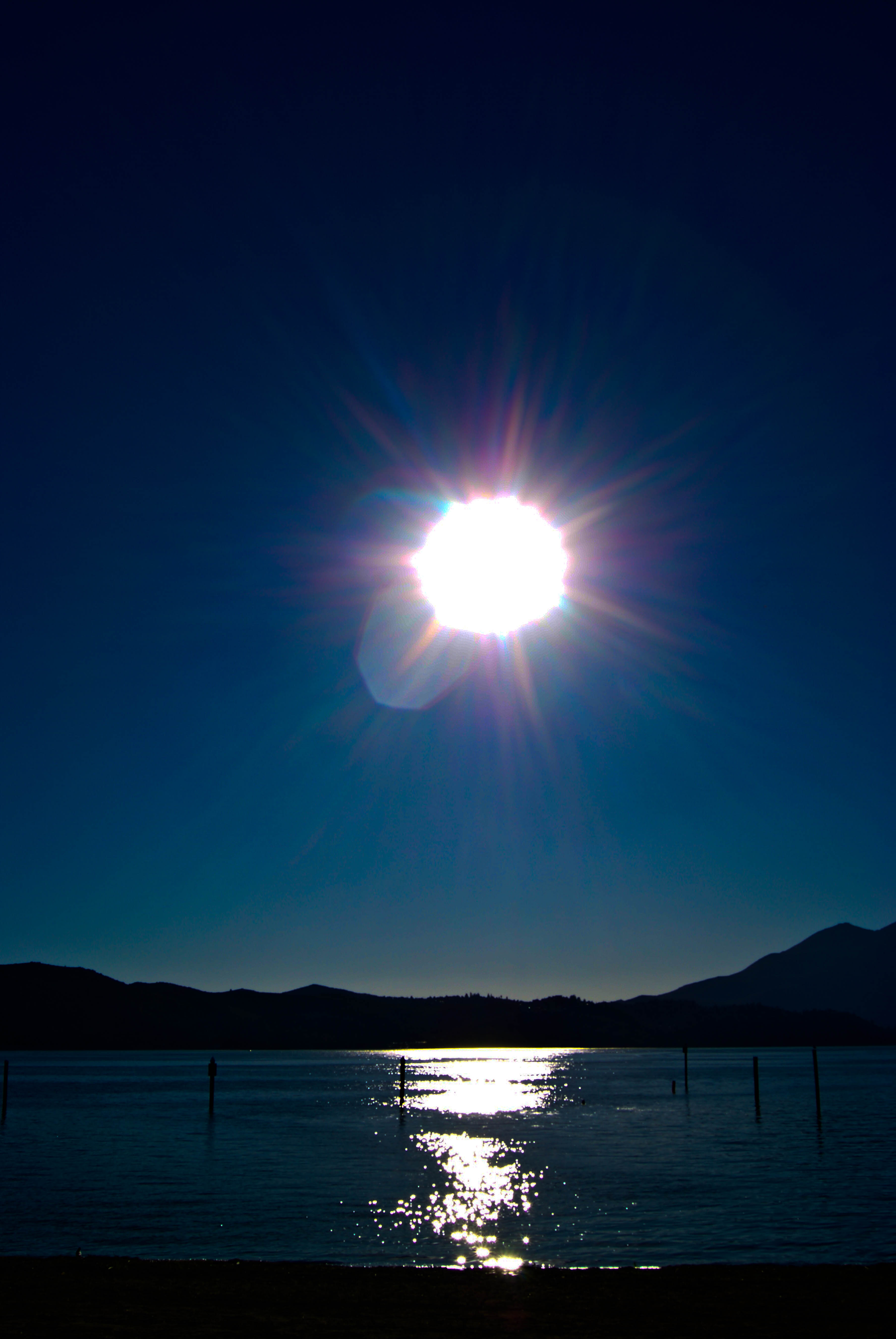 sun over the lake with mountains in the background